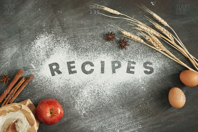 The word Recipes written in flour on a dark wood table with cake ingredients