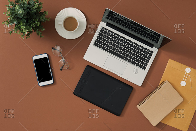 Photographer's work desk with camera and laptop on brown table