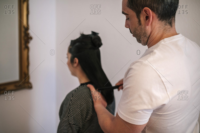 Father combing his daughter's hair to cut it at home