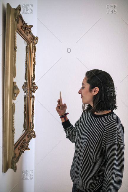 Young woman taking a selfie in a classic mirror in her living room at home