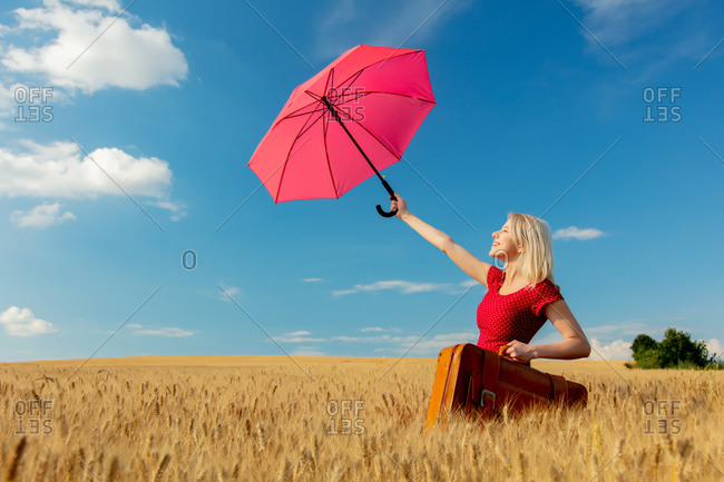 Blonde girl in red dress with umbrella and suitcase on wheat field