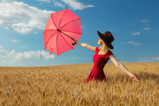 Blonde girl in hat and red dress with umbrella in wheat field