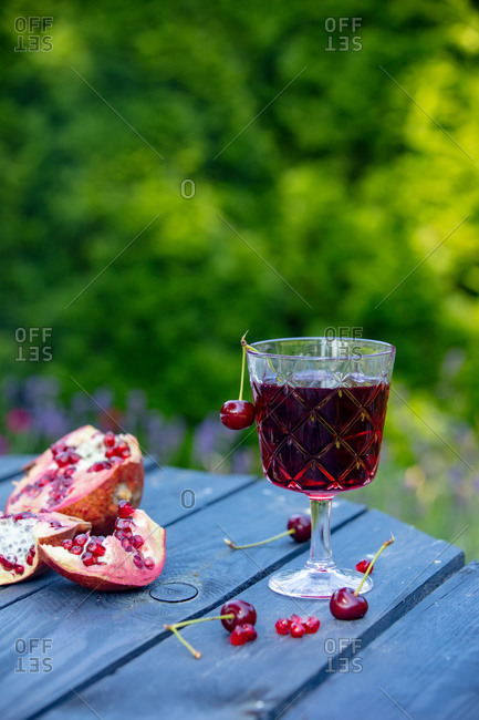 Sweet cherry and garnet cocktail on wooden table. Side view