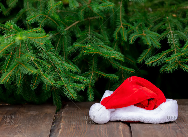 Santa Claus hat on a wooden table with pines on background