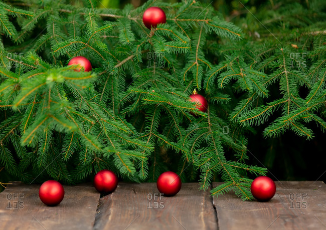Wooden table and Christmas tree with baubles on background