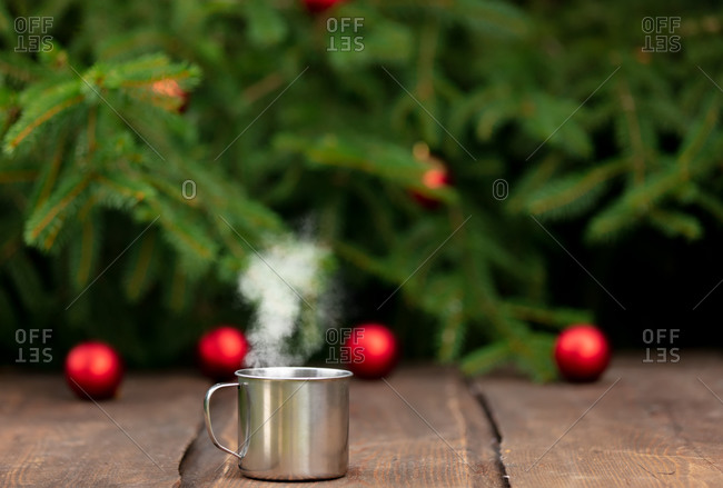 metal cup of coffee on a wooden table with Christmas tree and baubles on background