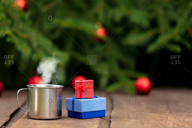 Cup of coffee and gifts on wooden table with fir tree and baubles on background
