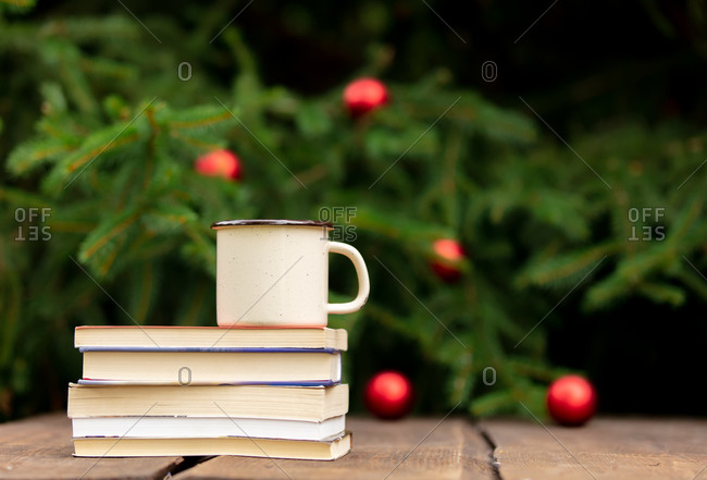Cup of coffee and books on wooden table with fir tree and baubles on background