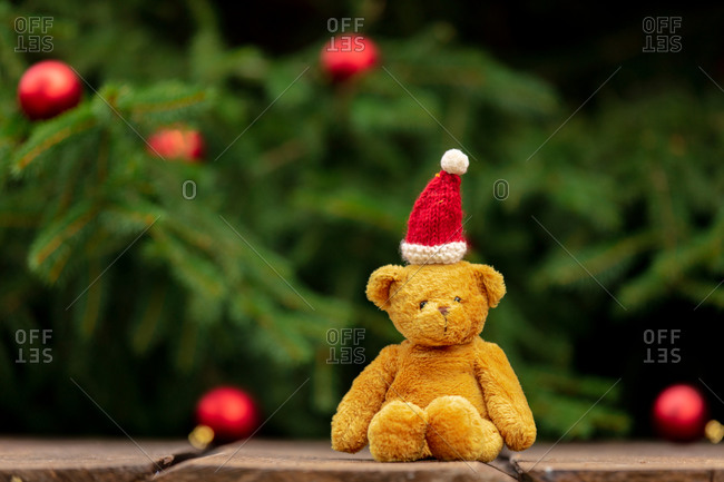 Teddy bear toy in Santa Claus hat on wooden table with Christmas tree and baubles on background