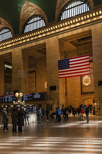 Midtown Manhattan, New York City, New York - February 22, 2020: Flag hanging above crowd in the main concourse at Grand Central Station