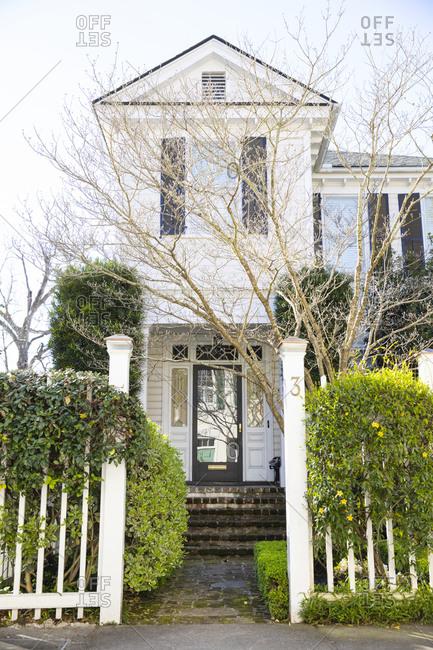 Charleston, South Carolina - March 6, 2019: White home exterior with green shrubs around entrance