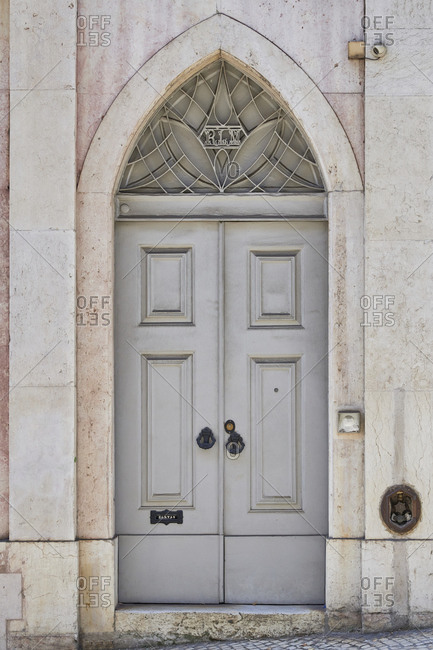 Lisbon, Portugal - July 15, 2020: Gray door with pointed arch in the Lapa neighborhood