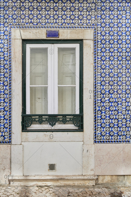 Home exterior with blue tile around the window on a home in the Lapa neighborhood, Lisbon, Portugal