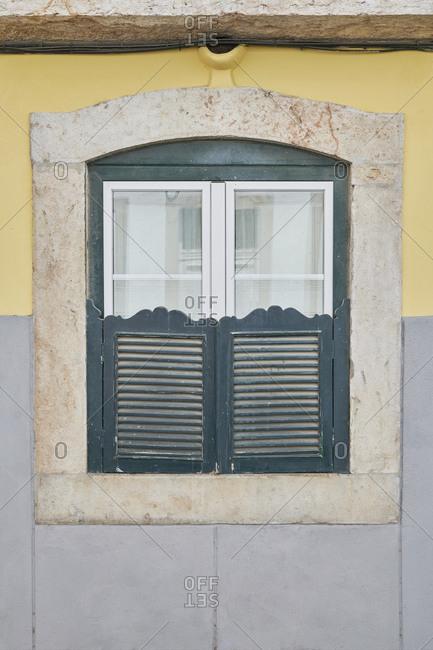 Blue shutters on a window in the Lapa neighborhood, Lisbon, Portugal