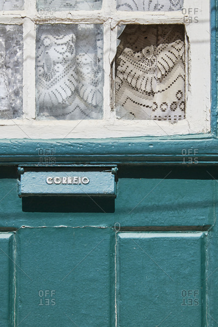 Blue painted wooden door with a letter box close up in Lisbon, Portugal