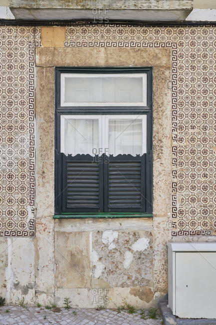 Home exterior with decorated old tile around window in the Lapa neighborhood, Lisbon, Portugal