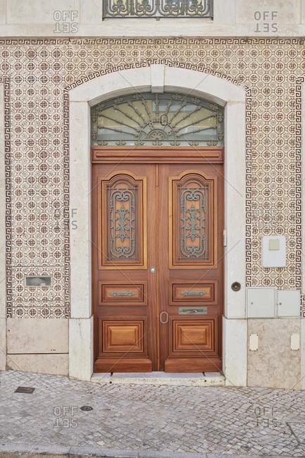 Wooden double door surrounded by Moorish tile in the Lapa neighborhood, Lisbon, Portugal