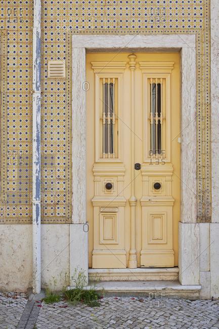 Yellow door surrounded by yellow Moorish tile in the Lapa neighborhood, Lisbon, Portugal