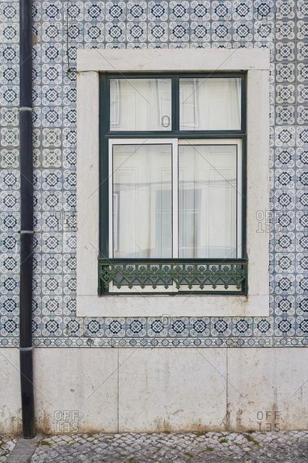 Home exterior with decorative tile surrounding the window, Lapa neighborhood, Lisbon, Portugal