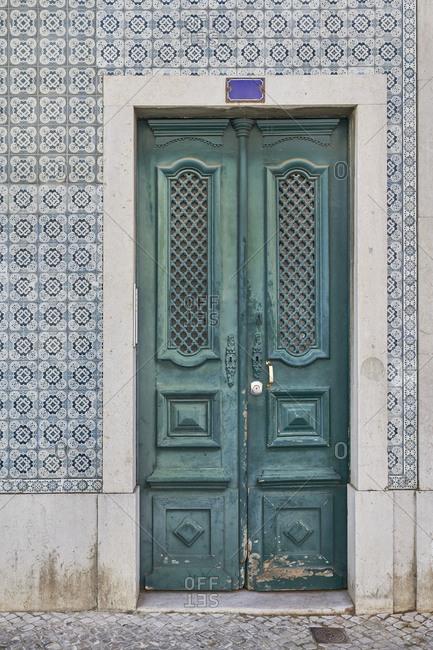 Home exterior with decorative tile surrounding a green door, Lapa neighborhood, Lisbon, Portugal