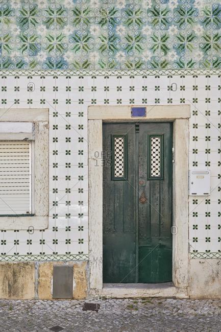 Home exterior with Moorish tile surrounding a green door, Lapa neighborhood, Lisbon, Portugal