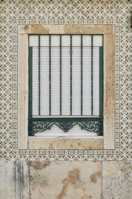 Decorative security bars on a window surrounded by tile, Lapa neighborhood, Lisbon, Portugal