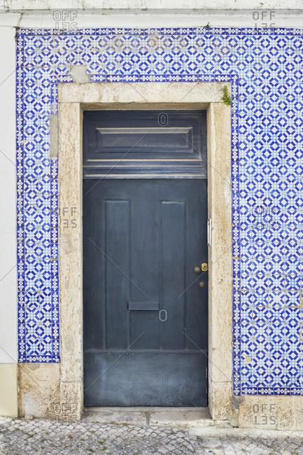 Blue door surrounded by bright blue Moorish tiles in the Lapa neighborhood, Lisbon, Portugal