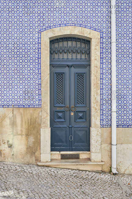 Blue door surrounded by blue Moorish tiles on a home in the Lapa neighborhood, Lisbon, Portugal