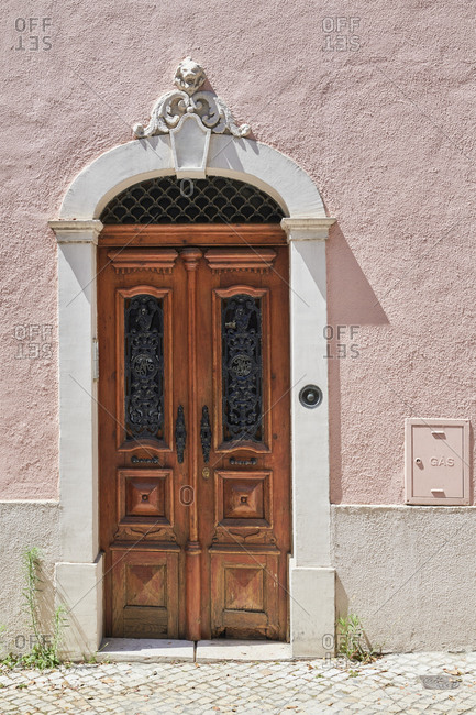 Wooden double door on a pink house in the Lapa neighborhood of Lisbon, Portugal
