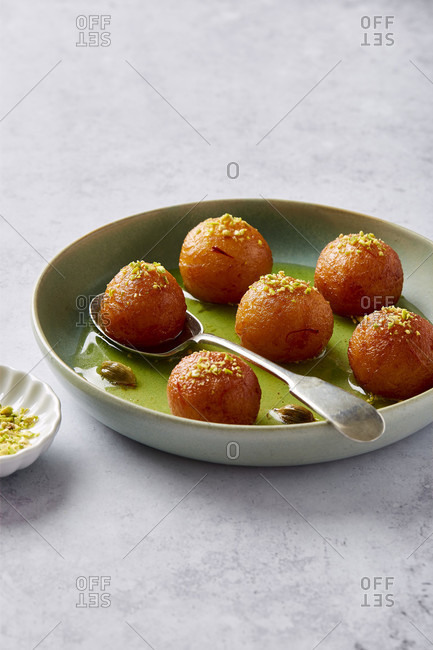 A bowl of Gulab jamun with pistachios