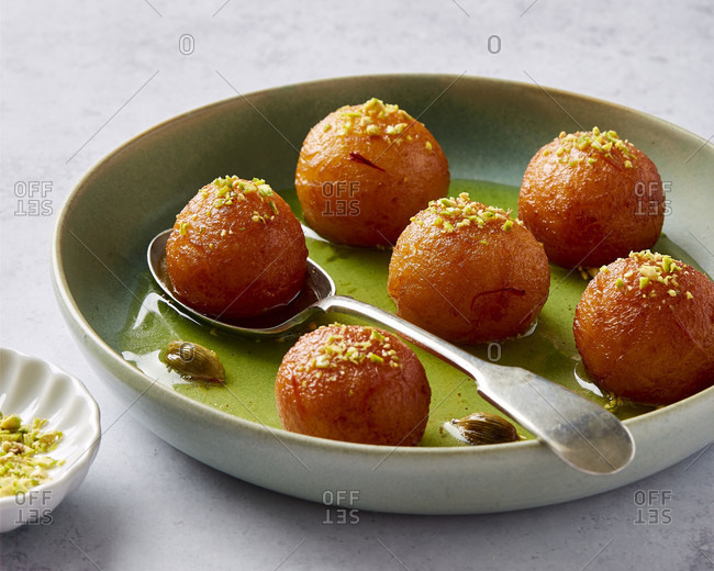 Close up of a bowl of Gulab jamun with pistachios
