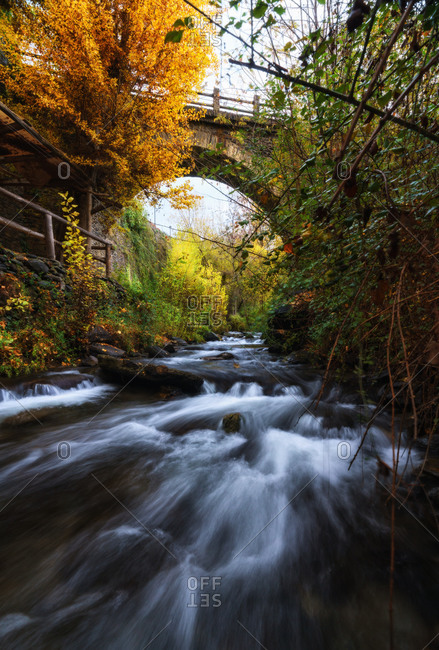 Majestic scenery of river flowing through forest and under bridge in long exposure in Granada
