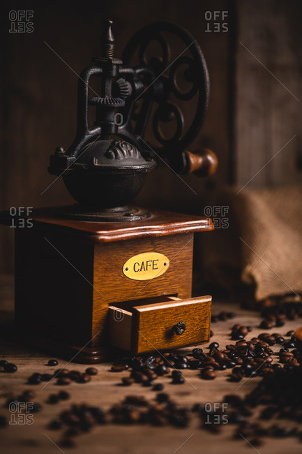 Retro coffee grinder placed on wooden table with scattered coffee beans in cafe