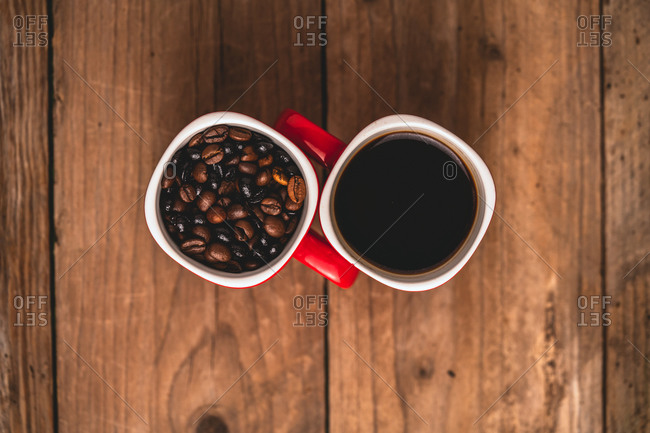 Top view composition of red cups with roasted aromatic coffee beans and fresh hot energizing americano placed together on wooden table
