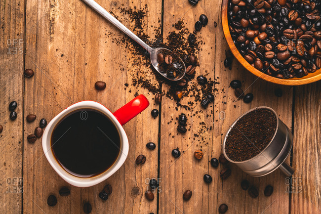 Top view of delicious beverage in mug placed on table with coffee beans and ground coffee in metal filter