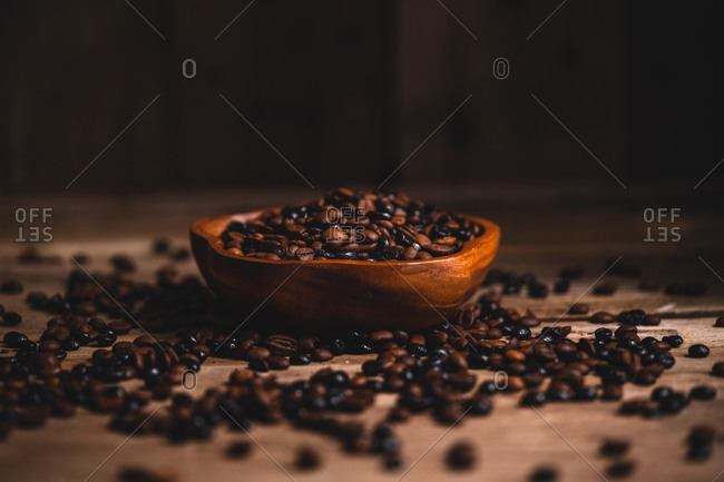 Aromatic coffee grains placed in bowl and scattered on table near vintage grinder