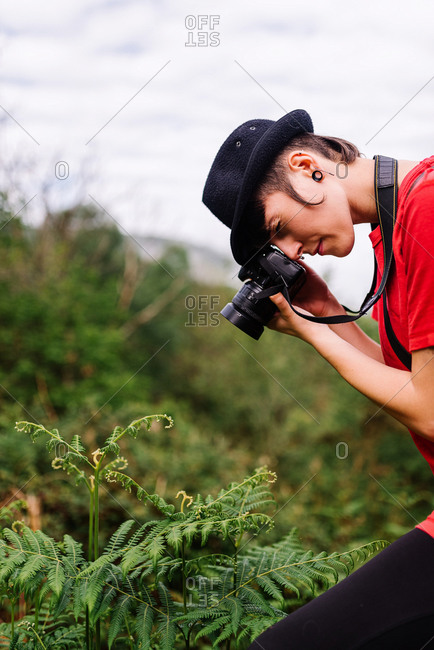 Side view of talented female photographer in trendy outfit taking photo of plant in field on photo camera