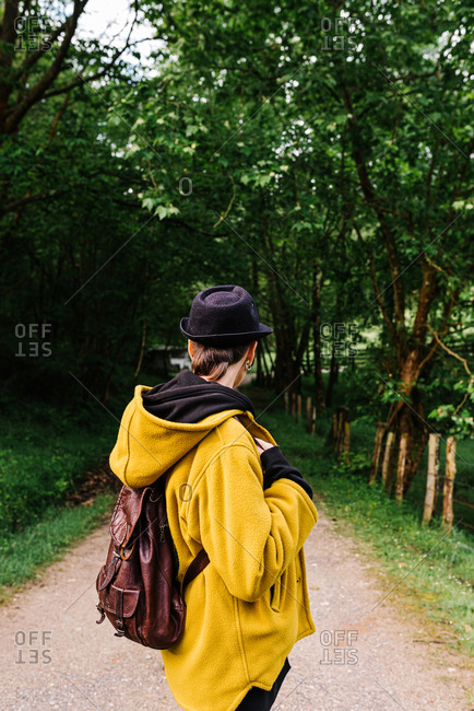 Back view of faceless female traveler with backpack standing along empty pathway surrounded by green trees on sunny day