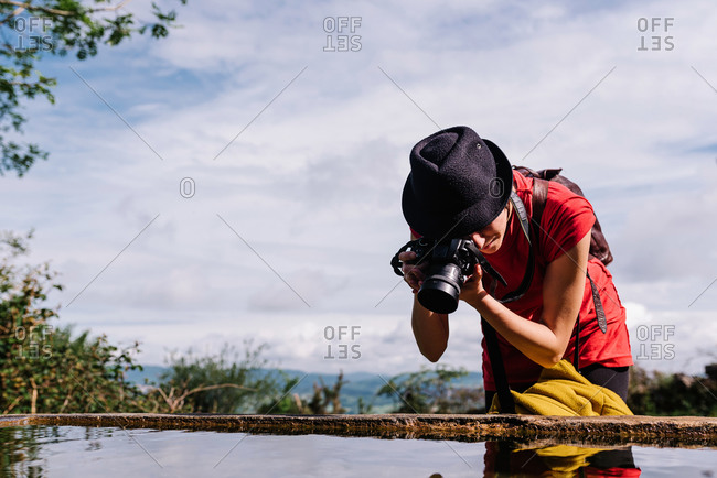 Androgynous female traveler in stylish clothes taking photo of reflection in water of pond during summer holiday in Asturias