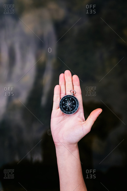 Top view of anonymous tourist standing with compass on hand on background of water surface