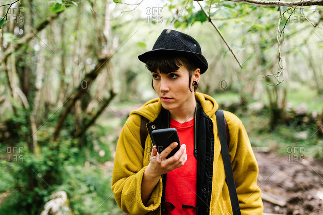 Tranquil female tourist standing in green woods with cellphone and looking away during vacation in Asturias