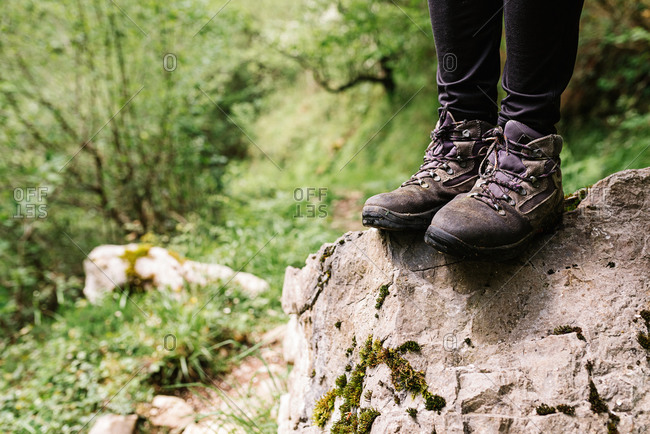Faceless hiker in footwear for trekking standing on rough stone during vacation in forest in Asturias