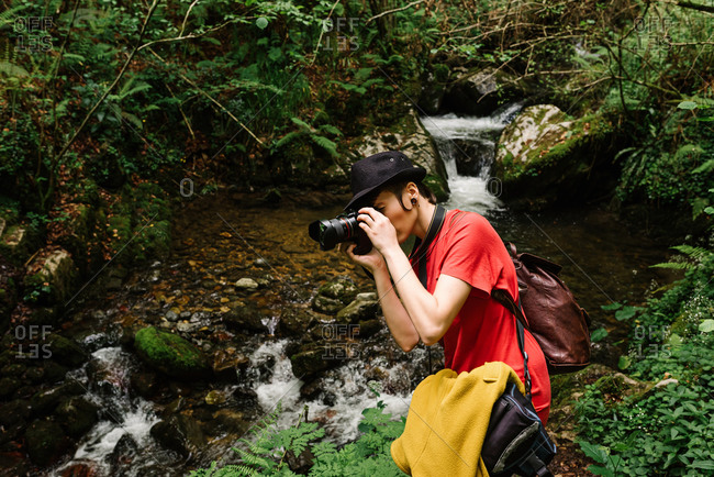 Side view of informal female traveler taking photos of nature on professional photo camera in woods during vacation