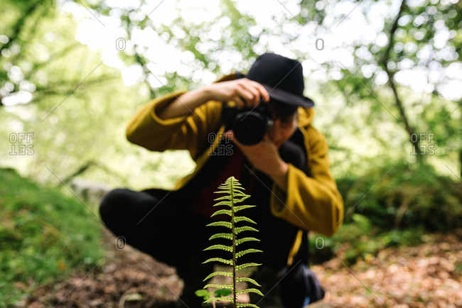 Talented female photographer in trendy outfit taking photo of plant in field on photo camera