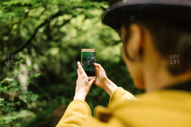 Back view of crop androgynous female tourist standing in green forest and taking picture of lush plants during holiday