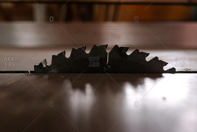 Detail of circular saw metal blade placed between wooden planks in carpentry workshop
