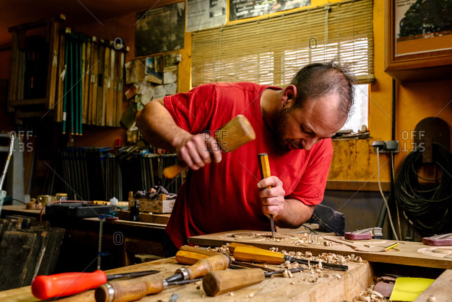 Talented craftsman standing at workbench and using chisel for wood carving in workplace