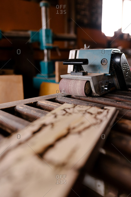 Professional belt sander machine placed on wooden table near timber plank in shabby workshop