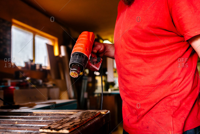 Unrecognizable male carpenter standing at workbench and drying piece of wood with professional heat gun