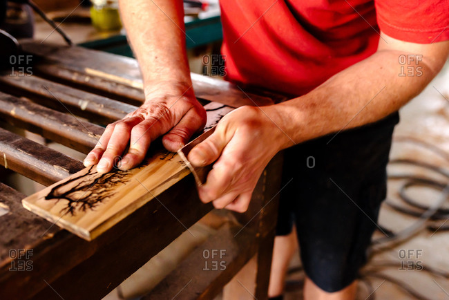 Faceless male woodworker standing at workbench and polishing timber board with sandpaper while working in workshop